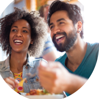 Man and woman smiling while eating salsa