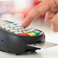 Hand pressing numbers on credit card processing machine with card in chip reader
