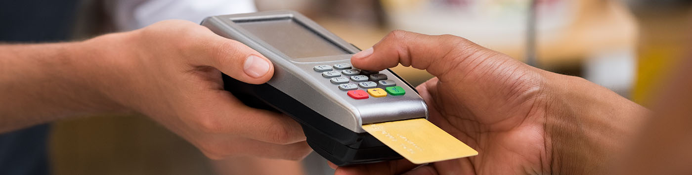 Hands holding credit card machine with card in chip reader