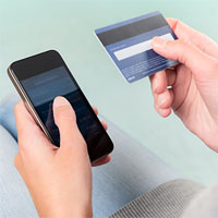 Hand holding phone and typing the information from the back of a debit card