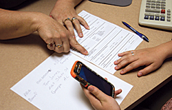 A hand gesturing to a document on a desk while another pair of hands is holding a smart phone