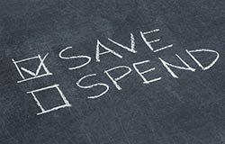 Written in chalk, there's a check marked box next to the word Save and an empty box by the word Spend.