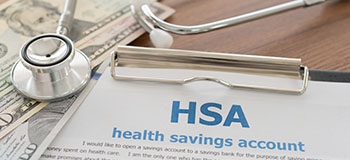 Photo of money, a stethoscope, and a document that reads HSA Health Savings Account