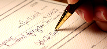 Close-up of someone signing a check
