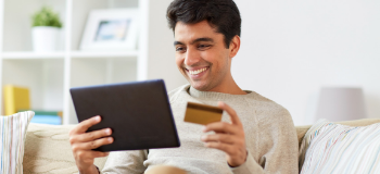 Man smiling at electronic tablet while holding a credit card