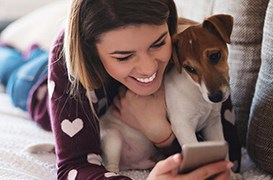 Happy girl with dog looking at phone