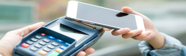 Phone held over POS machine for payment