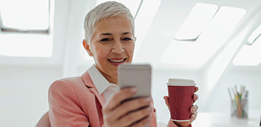 Older woman looking at cell phone with coffee in hand