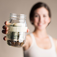 Smiling woman holds jar of money