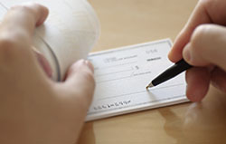 A close up of someone signing a check