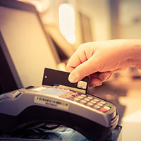 Hand swiping card through POS machine
