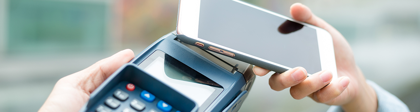 Phone held over POS machine in payment