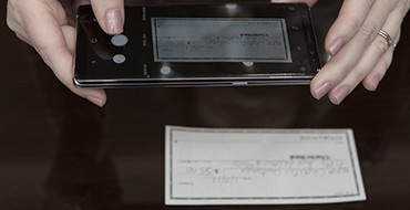 Hands holding phone and taking photo of a check