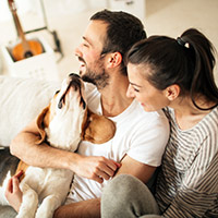 Couple laughing and snuggling a dog