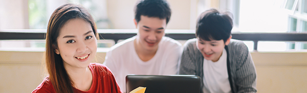 One young woman smiling at camera and two young men smiling at laptop