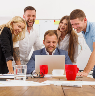 People smiling and laughing while looking at a computer